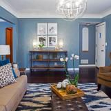 This living room boasts deep blue walls and crisp white molding. The furniture is arranged to invite conversation, and everything is tied together with a beautiful brown leather ottoman atop a dramatic blue and white patterned rug.