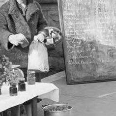 Bulletin board of prices at the Tuscaloosa curb market while a vender sells jellies, candies, vegetables and plants :: Alabama Cooperative Extension Service Photographs
