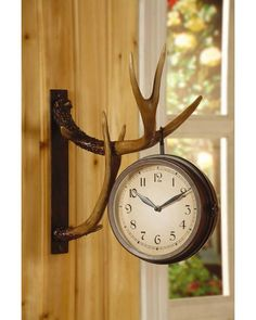 Hanging Double Sided Deer Clock - Unique double sided metal hanging clock with two faces on a resin cast wall mount with antlers. This would be a beautiful addition to any rustic or cabin design themed room.The rustic wall clock loops over cast-resin wall-mounted antlers to deliver a truly unique.