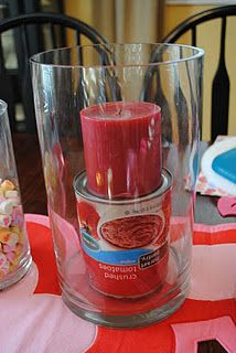 Place a can under the candle before adding decorative filler.  You'll use less filler and the candle will sit straight...
