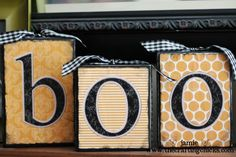 "Blocks of wood painted black, craft paper/letters painted over with ""modge podge"", Ribbon glued along edges"
