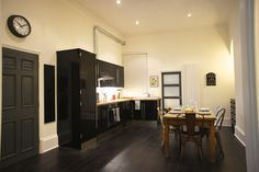 Black gloss kitchen, dark floors, farmer table, mismatched chairs, industrial ducting, white walls | Milsom View, Maple & Stone