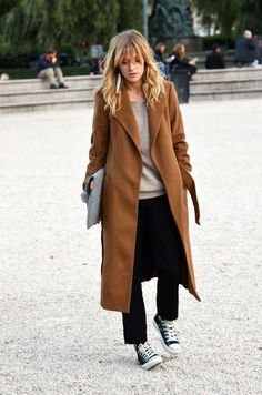 A brown coat and black suit pants couldn't possibly come across as other than strikingly elegant. Want to go easy on the shoe front? Rock a pair of black and white low top sneakers for the day.  Shop this look for $88:  http://lookastic.com/women/looks/earrings-crew-neck-sweater-coat-dress-pants-low-top-sneakers/6329  — White Earrings  — Grey Crew-neck Sweater  — Brown Coat  — Black Dress Pants  — Black and White Low Top Sneakers
