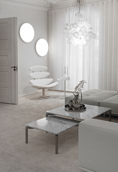 bright living room design with white walls, small coffee tables and from floor to ceiling white curtains