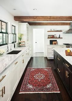 Well appointed black and and white kitchen features a red wood rug placed in front of white shaker cabinets adorning brass pulls and a white quartzite countertop fitted with a stainless steel undermount sink paired with a polished nickel pull down faucet fixed in front of black framed windows.
