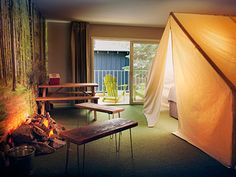 At Basecamp Hotel in South Lake Tahoe, California, lodging options include a canvas tent over the bed, a faux campfire, and glow-in-the-dark stars on the ceiling.