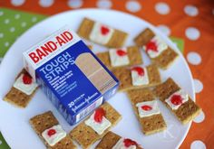 """Here's a terrific treat the kids will love -to make fun of! But they'll end up eating them as well, yelling """"Ewww"""" the entire time. The recipe for Used Band-Aids is simply cinnamon graham crackers with some frosting for the pads, and maybe a bit of gross red jelly or jam in the middle"""