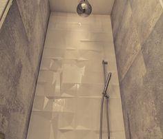 Nowoczesny prysznic z designerską deszczownicą w kształcie kropli deszczu.