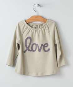 A wonderful top for your little that shows how much love they have to give! This elegant color goes with nearly any Valentine's Day outfit you can come up with and the big embroidered LOVE word on the front helps her stand out in any gathering or photo. The partially gathered neck line provides an extra dressy look. A Hallmark Baby exclusive for the winter, so get yours before they sell out!