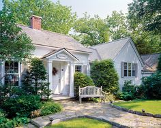 The original cottage is still the home's welcoming entry. Charmed by the storybook path and sweet sign above the door, visitors don't notice how the pretty place rambles. Instead, house and site make a happy, timeless union.
