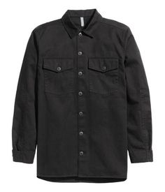 Nearly black. Shirt jacket in cotton twill. Chest pockets with flap and button, buttons at cuffs, and reinforced panels in matching fabric under arms.
