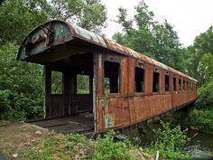 Bočný pohľad na vagón. Vidno, že je tu už dlho, je celý zhrdzavený a prehnutý.