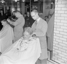 "A PICTURE OF A SOUTHERN TOWN: LIFE IN WARTIME READING, BERKSHIRE, ENGLAND, UK, 1945."". "".© IWM (D 25462)IWM Non Commercial Licence  Customers receive haircuts at Thomas's barber shop in Reading. According to the original caption, ""shortage of staff has led to long waits, has made the barber shop even more of a man's club than it was before the war""."