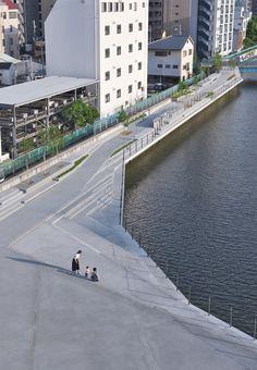 川沿いの遊歩道を進むと、ひな壇状の構造物が連続する広い空間が現れた(写真1、写真2)。転落防止柵のワイヤ越しに、川面を泳ぐ小魚の群れが見える。大阪府西大阪治水事務所が大阪市西区の木津川左岸に整備中の「木津川遊歩空間」で、この3月に他に先行して供用スタートしたエリアだ。