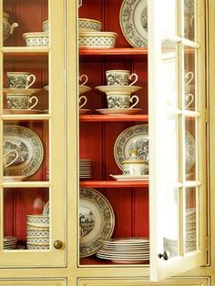 Color Contrast ~ Painting the interiors of shelves and cabinets helps set off prized collections. Black-and-white china gets a shot of interest when arranged in front of the coral-hued backdrop.