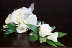 These are white dendrobium orchid blooms with the spray roses, and the corsage is on a pearl wristlet. Description from martinflowers.com. I searched for this on bing.com/images