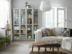 Ein kleines Wohnzimmer u. a. eingerichtet mit BILLY Bücherregalen mit Glastür in Beige, einem hellen Sofa und Satztischen in Nussbaumfurnier