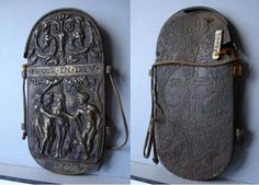 """eyeglass case and nose spectacles E Cl 21.022 dated """"1580"""" """"belt-case"""" because it was made to hang from the waist, bronze, the front side represents on the lowest part """"1580"""", above that is the Judgment of Paris (not the town), above which is the text """"trust in God"""".   Above that is a skull, ornaments and leaves, also two horns and two faces."""
