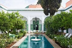 Mandarin-orange trees and 'Iceberg' roses flourish in the courtyard of a Marrakech house that belonged to the late Chilean artist Claudio Bravo. The property was inherited by one of Bravo's friends, who called on Sardar Design Studio to renovate it as a vacation home for her family. The swimming pool features a 19th-century Indian fountain.