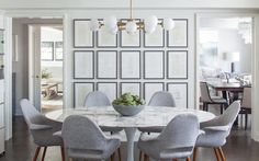 A white glass and brass globe chandelier hangs over a Saarinen Oval Dining Table surrounded by 6 Saarinen Executive Armchairs with Wood Legs placed in front of a wall covered in black framed stacked art.