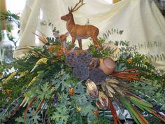 Casket spray made for the outdoorsman with permanent greenery and natural dried florals, a deer family was added here to represent an interest. This can also be a column arrangement. $175.00
