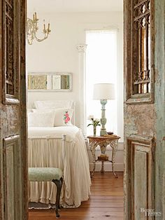 Antique doors replete with rusty grilles and worn green paint enclosing a bedroom doorway evoke images of medieval entries and secret garden gates. A vintage baluster shines as a bright light thanks to a lamp-wiring kit, some expert drilling, and a simple white drum shade. An old column beefs up the window trim./