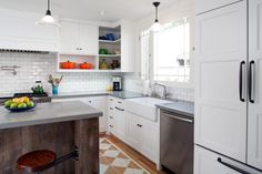 Designer Jeff Troyer combined the former dining room and pantry to create a large, open kitchen with a rustic reclaimed wood island. The gray countertops, white cabinetry and white subway tile backsplash are enlivened with pops of color from a collection of vibrant kitchenware showcased on open shelving.