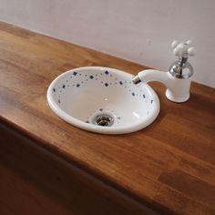 かわいい陶器のボウルの手洗いトイレは狭い空間ではありますが狭いからこそ他の部屋では採用しにくいかわいいインテリアパーツやインテリアカラーを楽しむことができる空間です . フレンチナチュラルスタイルの家のトイレは陶器のハンドルの水栓ですブルーの模様が入った白のボウルもとてもかわいいですね . 子どものいる家庭だとタンクに手洗いがあるトイレは手を洗う時に水を飛ばしてしまいますし遠くて子どもには使いにくいと言われています カウンターに設けた手洗いなら洗いやすいのでおすすめです
