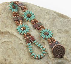 A charming bracelet floral design beaded with Czech glass beads. The floral motifs consist of turquoise picasso Super Duos surrounding a