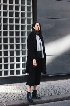 Elisa from the Fashion- and Lifestyleblog www.schwarzersamt.com is wearing an autumn winter look with black culotte from Topshop, a Topshop sweater in light grey, a black coat from H&M and black high chelsea boots. The whole look is monochrome in black and grey.