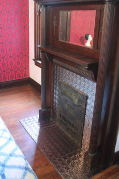 Pressed tin covered fireplace... hides ugly tile work. Amy Rikhoff ...