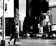 Times Square. A man at an intersection. by Mitsushiro Nakagawa