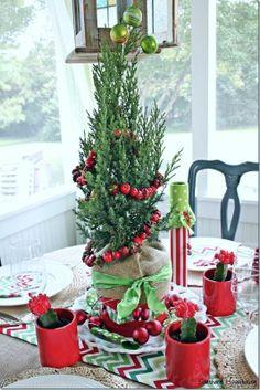 Fun and festive Christmas centerpiece idea using Christmas cacti, an evergreen shrub, and berry garland.