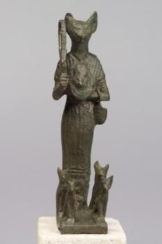 Ancient Egypt. Carved black limestone cat-headed Goddess Bastet, one knee up and wearing a kilt, seated on a base. Dirt patina. Ptolemaic. 305-30 BC
