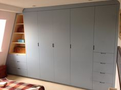 Bespoke loft conversion wardrobe made from birch plywood and Dove Blue doors.