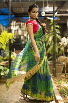 DESCRIPTION: Did somebody say 'Shibori'? We cannot stop crushing on all manner of attractive Shibori dyed ware! Two thumbs up to this Shibori dyed green drape in semi kota doria fabric. You are bound to look forever trendy in this beautiful saree. Red and green are a magical pairing! Or stay cool as ever in a green blue or a yellow blouse.ACCOMPANIMENTS: All sarees are sold completely finished with falls and a free size underskirt. FABRIC: Saree - Green yellow shibori dyed semi kota doria…
