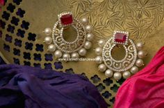 gold chand bali earrings studded with precious diamonds and a square cut ruby in fancy ear stud design edged with pearl drops.