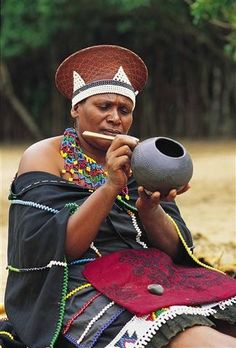 A married Zulu woman wearing a traditional hat, cloak and necklace is painting a pot. South Africa A married Zulu woman wearing a traditional hat, cloak and necklace is painting a pot. Zulu Women, African Women, African Fashion, South African Tribes, Safari, Art Tribal, Xhosa, World Crafts, Kwazulu Natal