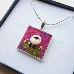 An original hand crafted miniature collage felted and embroidered on wool felt by textile artist Maxine Smith. Shropshire-based textile artist Maxine creates unusual original pieces of fabric art inspired by the hillsides and hedgerows of Shropshire. The pendant is made using hand-dyed wool felt and detail has been added using needle felting and hand embroidery. Both the pendant and chain are silver plated. The pendant is approximately 2.5cm x 2.5cm / 1 inch x 1 inch. Chain measures 1...