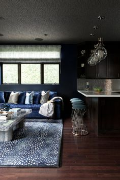 Rich hardwood flooring connects the contemporary living room and kitchen in this open design. A dark ceiling and navy-blue walls create a sultry background and allow the natural light from the window to shine extra bright and illuminate the sheen in the throw-pillow fabric.