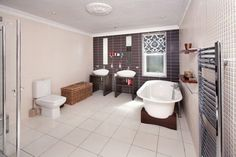 Muse bassist Chris Wolstenholme put his hometown property on the market for a (relatively) modest £895,000 back in 2010. This stunning tiled bathroom is a great example of what you can do without cluttering the area, with a gleaming towel rail seen in the foreground, and individual countertop basins against the back wall.
