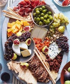 This cheese board by @whatgabycookin is decorated with figs and is loaded with crackers, grapes and breadsticks