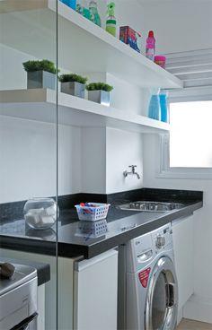 A claridade da lavanderia atravessa a divisória de vidro temperado e chega à cozinha. Projeto de Renata Cáfaro.