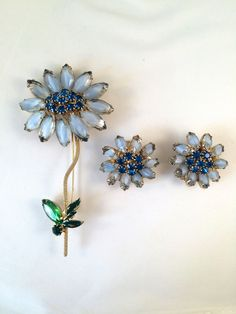 Spring fling! This gorgeous WEISS white flower pin and matching earring set features the WEISS iconic smoky rhinestones in marquise shape as the petals and vibrant blue rhinetones illuminate the center of the flower. The pin is even embellished with a textured gold toned metal vine connecting itself to the green marquise rhinestone and prized enameled metal leaves. #weiss