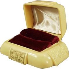 This old, cream colored plastic ring box has embossed panels on the sides and a gold design panel on the front and top. Inside is a maroon velvet