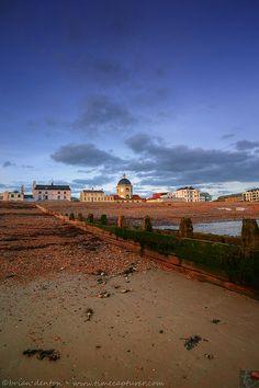 De tide has receded n left seaweed on de beach with de seafront buildings n de distinctive Dome Theatre in de town of Wortthing in West Sussex, England_ UK