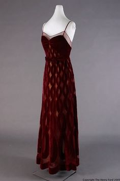 """Evening Dress, 1940, by Jean Patou. Clothing label on dress: """"Jean Patou/PARIS."""" Clothing label on gold underdress: """"BERGDORF-GOODMAN/FIFTH AVENUE AT 58TH STREET."""" Handwritten on tag sewn on back of label: Mrs. H. Fireston/10-16-40/64211. The velvet portion of this dress was made by Jean Patou and the gold lame cloth that shows through the cut-outs is from Bergdorf-Goodman."""