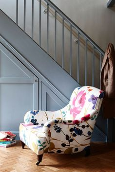 A deep grey shade provides the perfect foil for a comfy armchair upholstered in a striking oversized floral fabric. Photography: Joanna Henderson. Find more hallway ideas at housebeautiful.co.uk