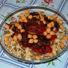 Rice, lentils, macaroni, browned onions, and tomato sauce are prepared separately, then spooned in layers on servings plates in this traditional Egyptian vegetarian meal.