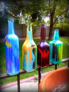 DIY Painted Liquor & Wine Bottles: Squirt paint into empty clean bottles and shake, twist, wave around till the interior is covered with color -  I just did these this afternoon in about 30 minutes - they look so cool!